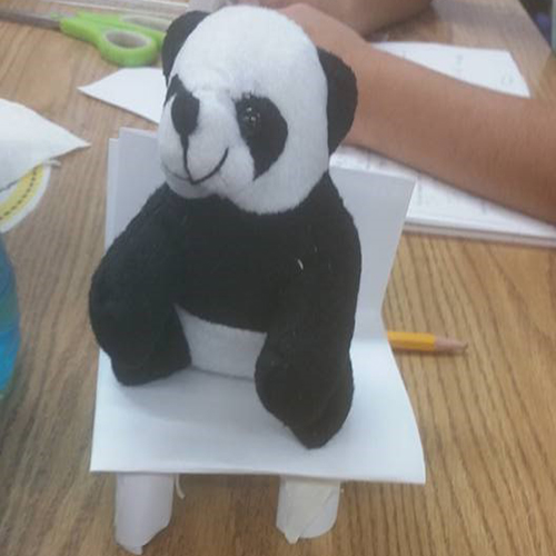 A photo of a toy panda sitting on a chair