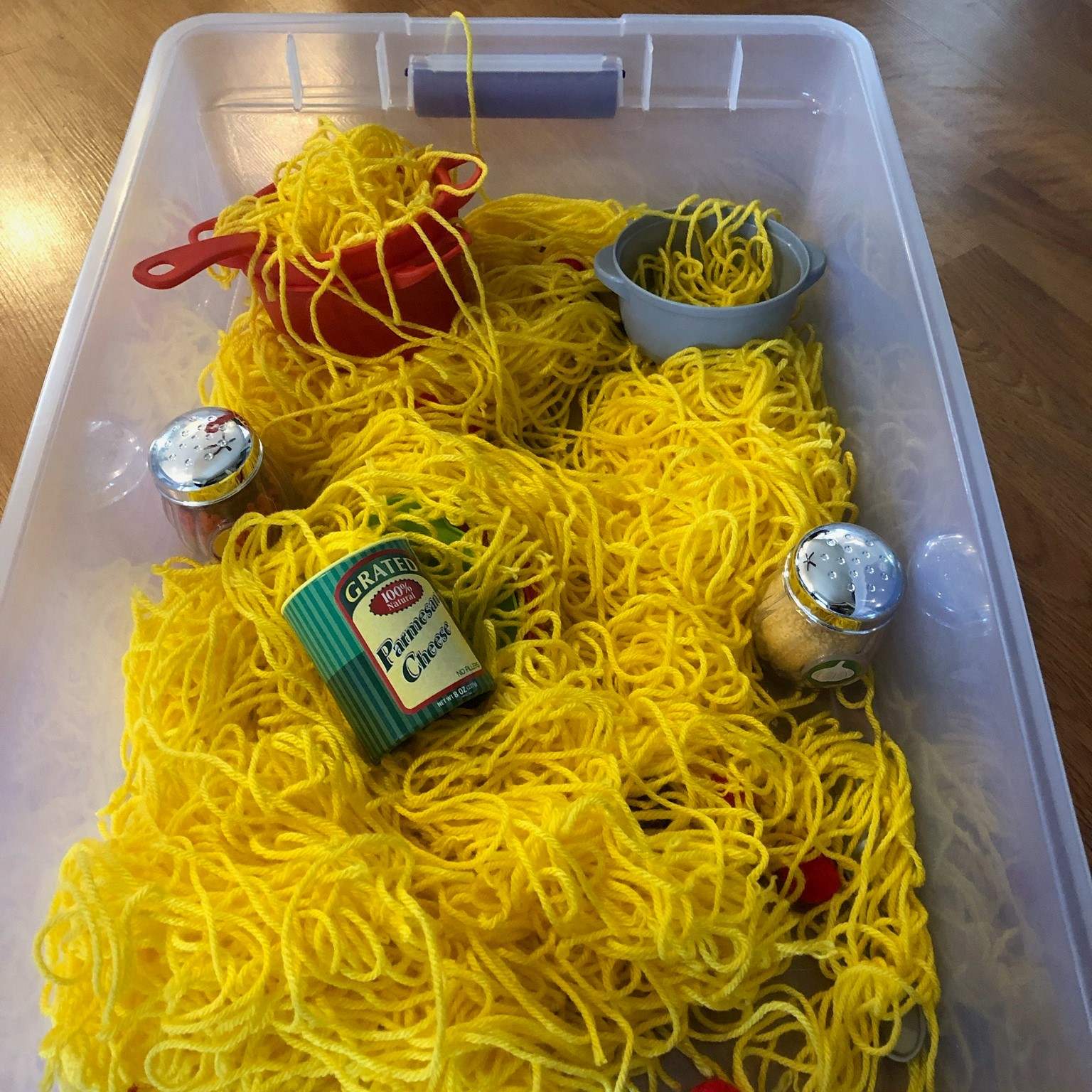 A sensory bin filled with yarn, cans, colander, and condiment shakers