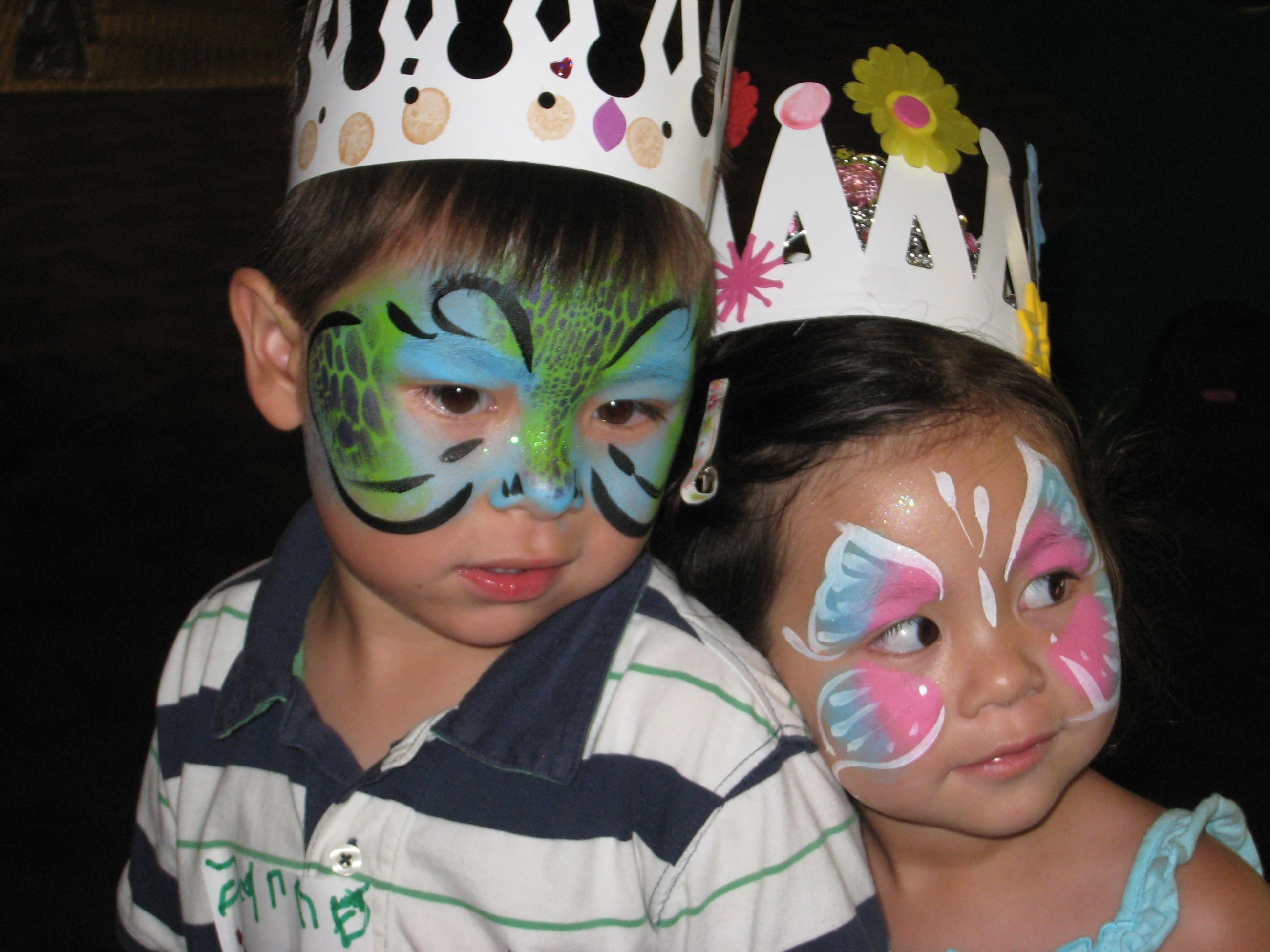 Two children with their faces painted wearing crowns