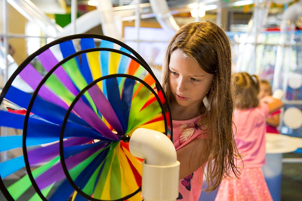 Girl examines spinning wheels